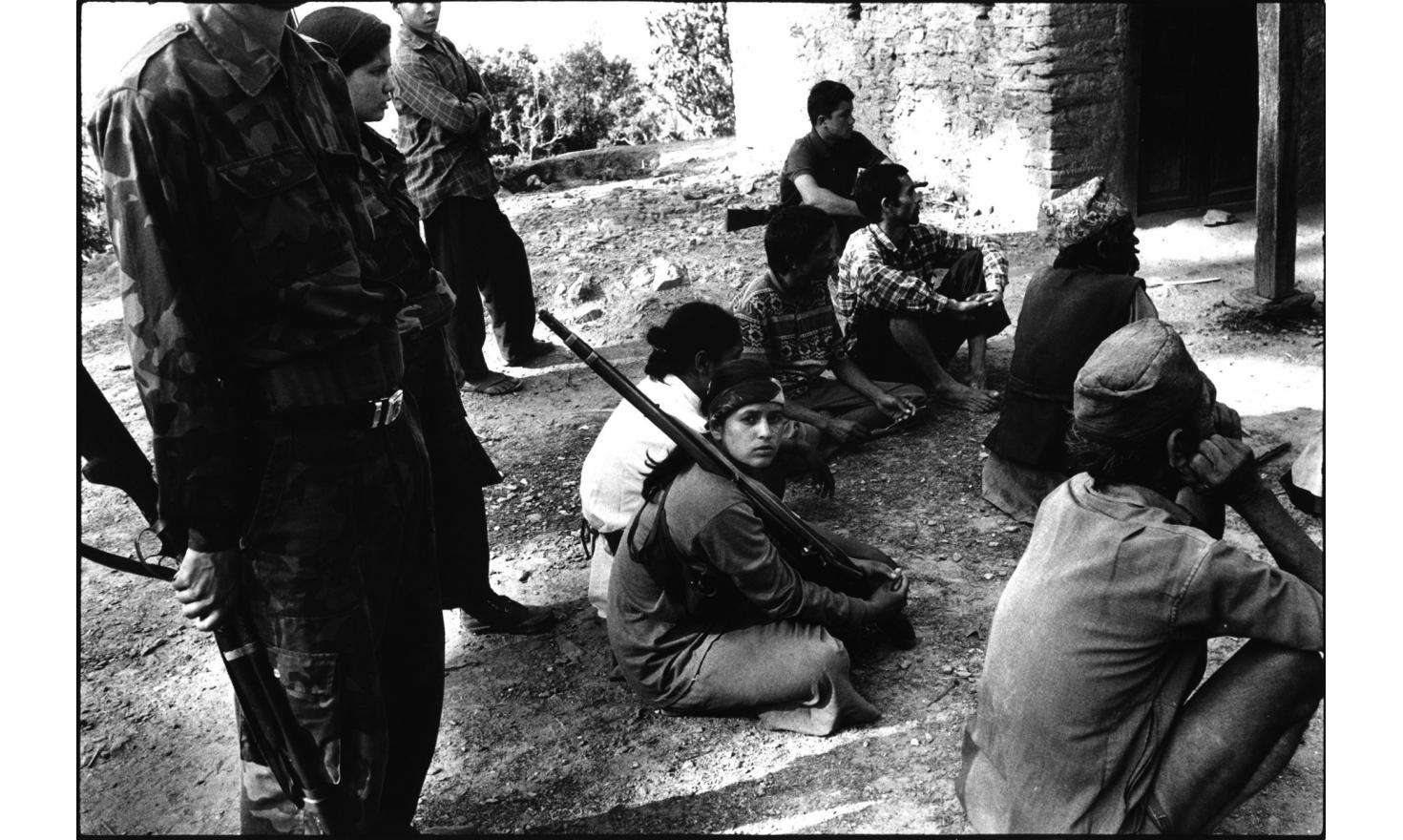 The young Red Army soldiers are in charge to prevent the Malika villagers from leaving the meeting for the local Maoist government elections (7 hours) on the 25th of May 2001. In the center, Radha, red Army 16 years old.
