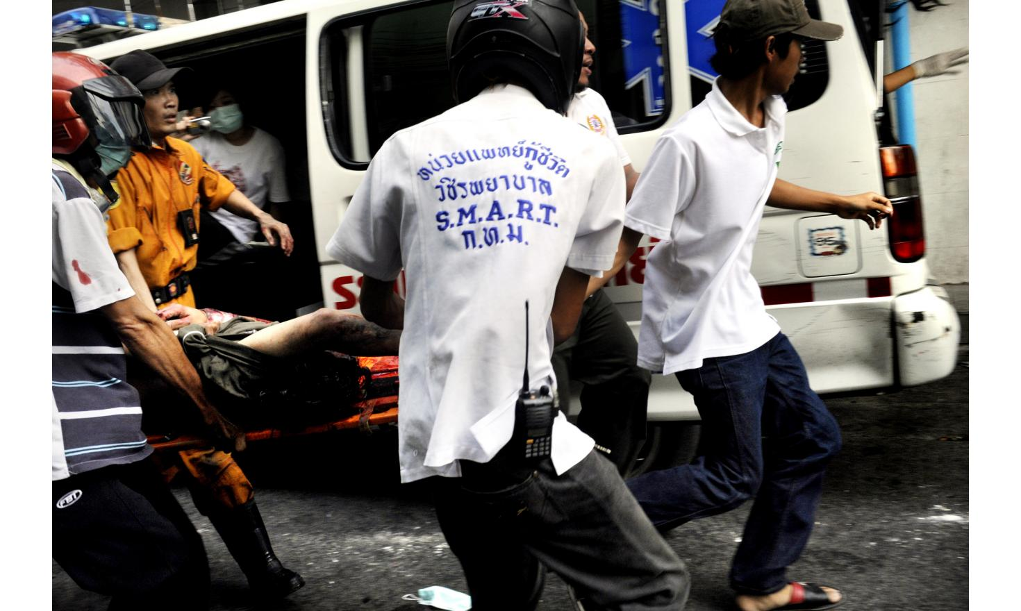 Thai medic teams pull out a red shirt protestor injured during clashes with Thai Army on Nang Duplee street, corner of Rama IV road, Bangkok Thailand
