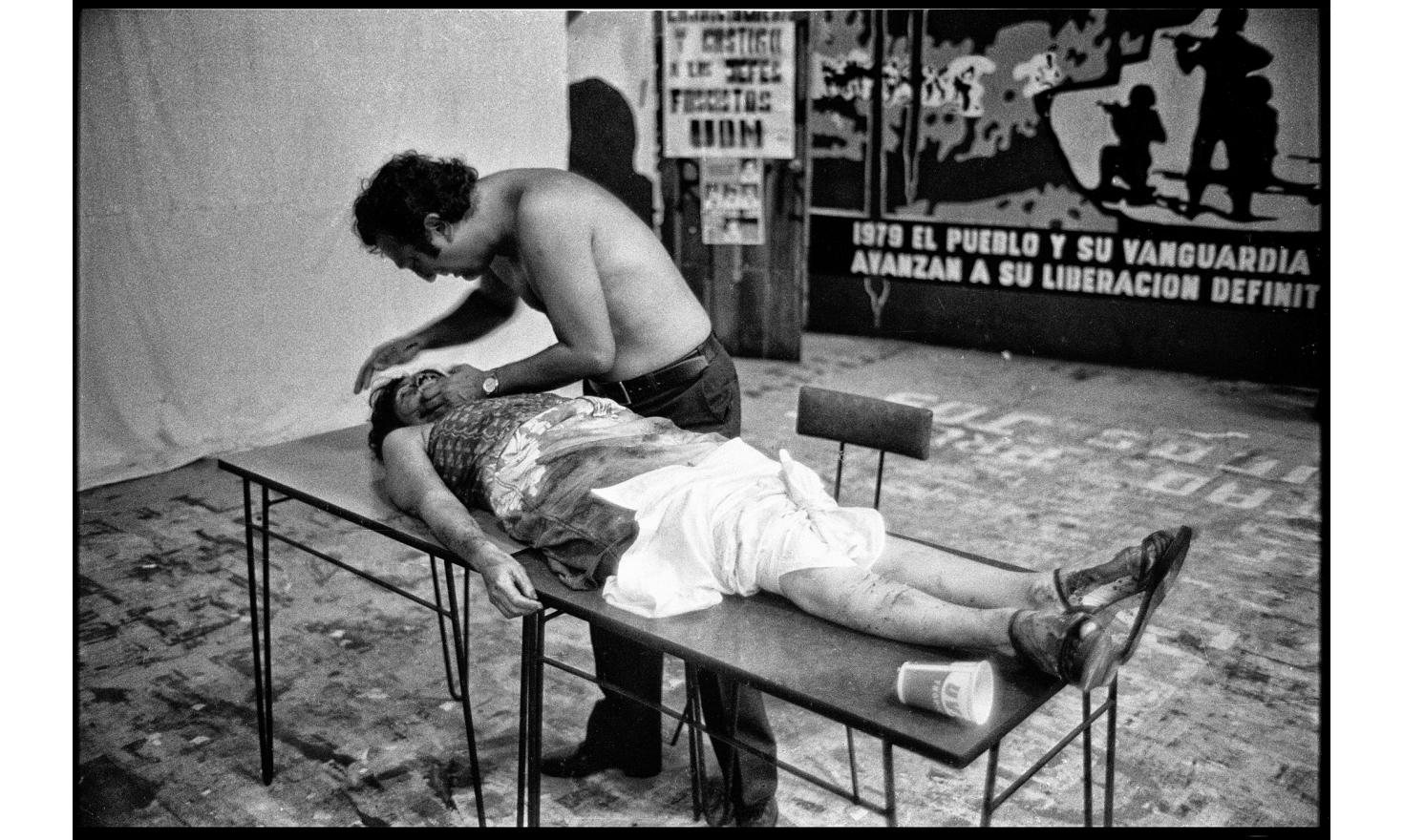A woman has been shot dead during a demonstration. A crying man puts his shirt on her legs. San Salvador. October 1979