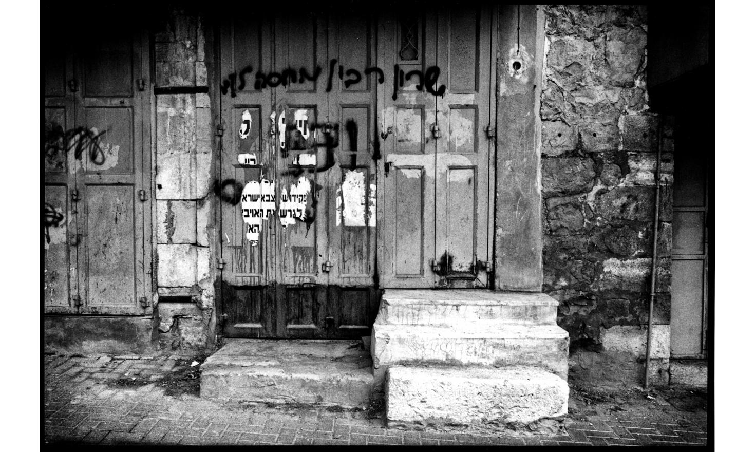 "In the bazaar, occupied by settlers, there are hostile inscriptions to the Pr. Minister, painted on doors of closed Arab shops, it is written: ""Sharon, Rabin is waiting for you"": 6 weeks later, A. Sharon was struck by a cerebral attack. Hebron, Nov. 2005"