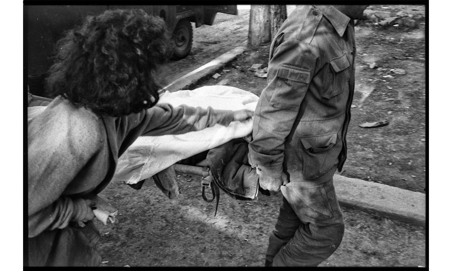 A woman is covering the face of a dead fighter. Stepanakaert, Nagorny Karabakh. 04-1994