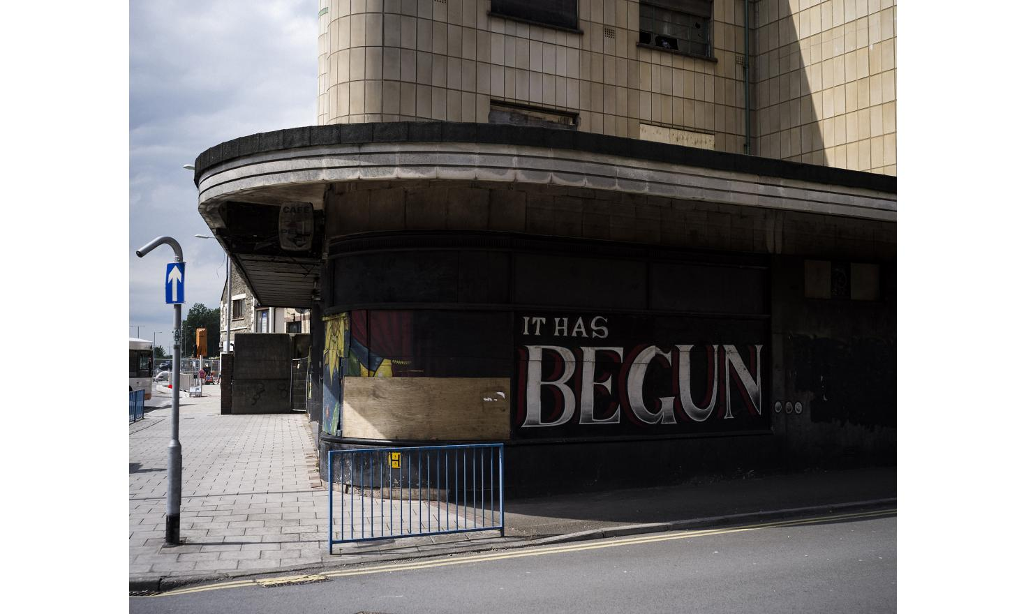 """Graffitti on the side of a closed-down cinema in Port Talbot, South Wales reads, """"IT HAS BEGUN..."""". The once-affluent town is in decline."""