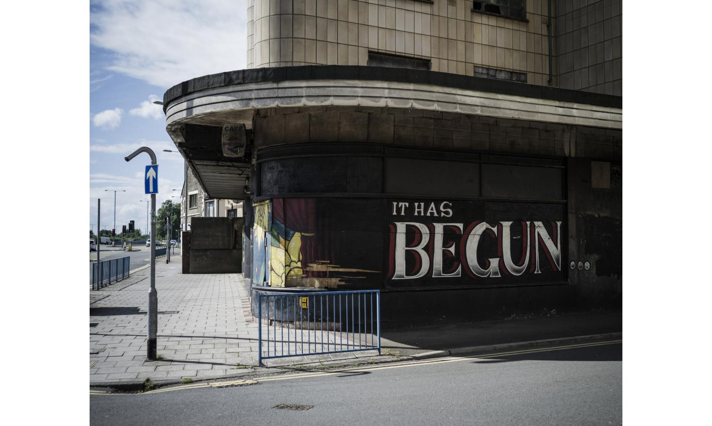 """Graffiti reading, """"It has begun..."""" on the wall of a closed-down cinema in Port Talbot, Wales. The town depends upon steel for much of it's economy is in economic difficulty because of Chinese steel dumping."""