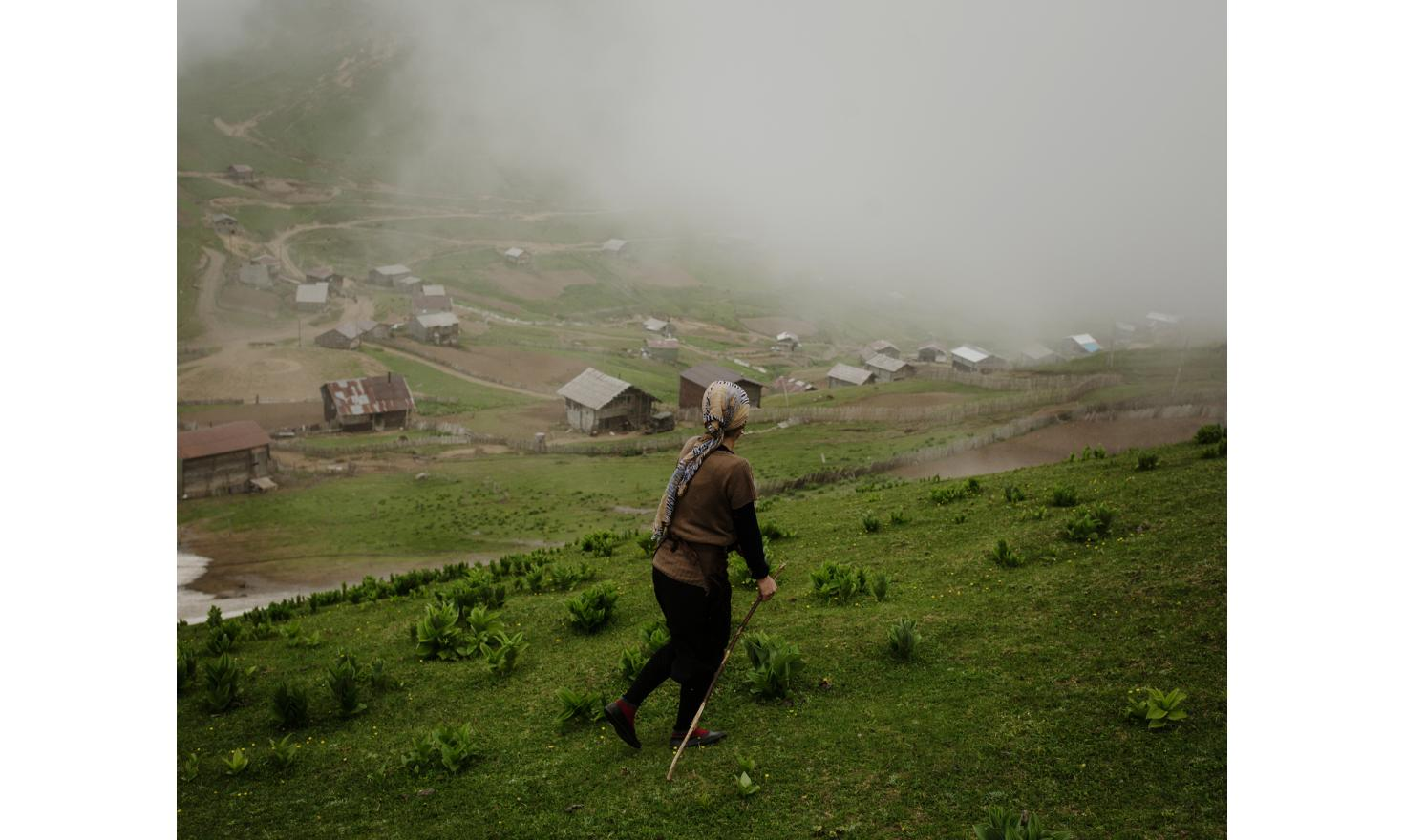 Zortikheli. A woman goes and pick her animals while clouds arrive on the village and rain threatens.