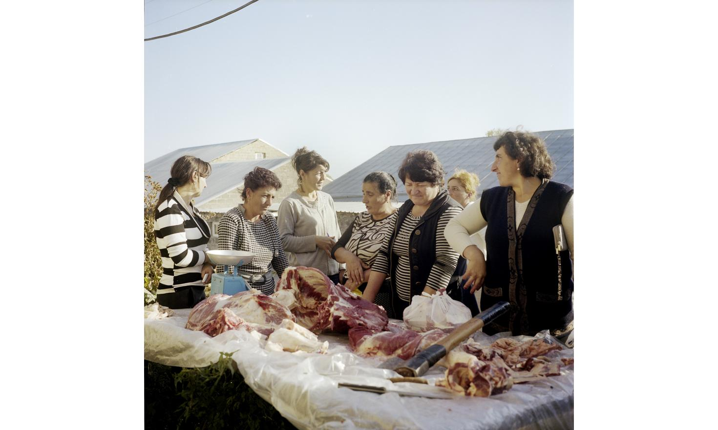 The morning. A butcher just killed two calves of a local woman, so women join to buy meat.