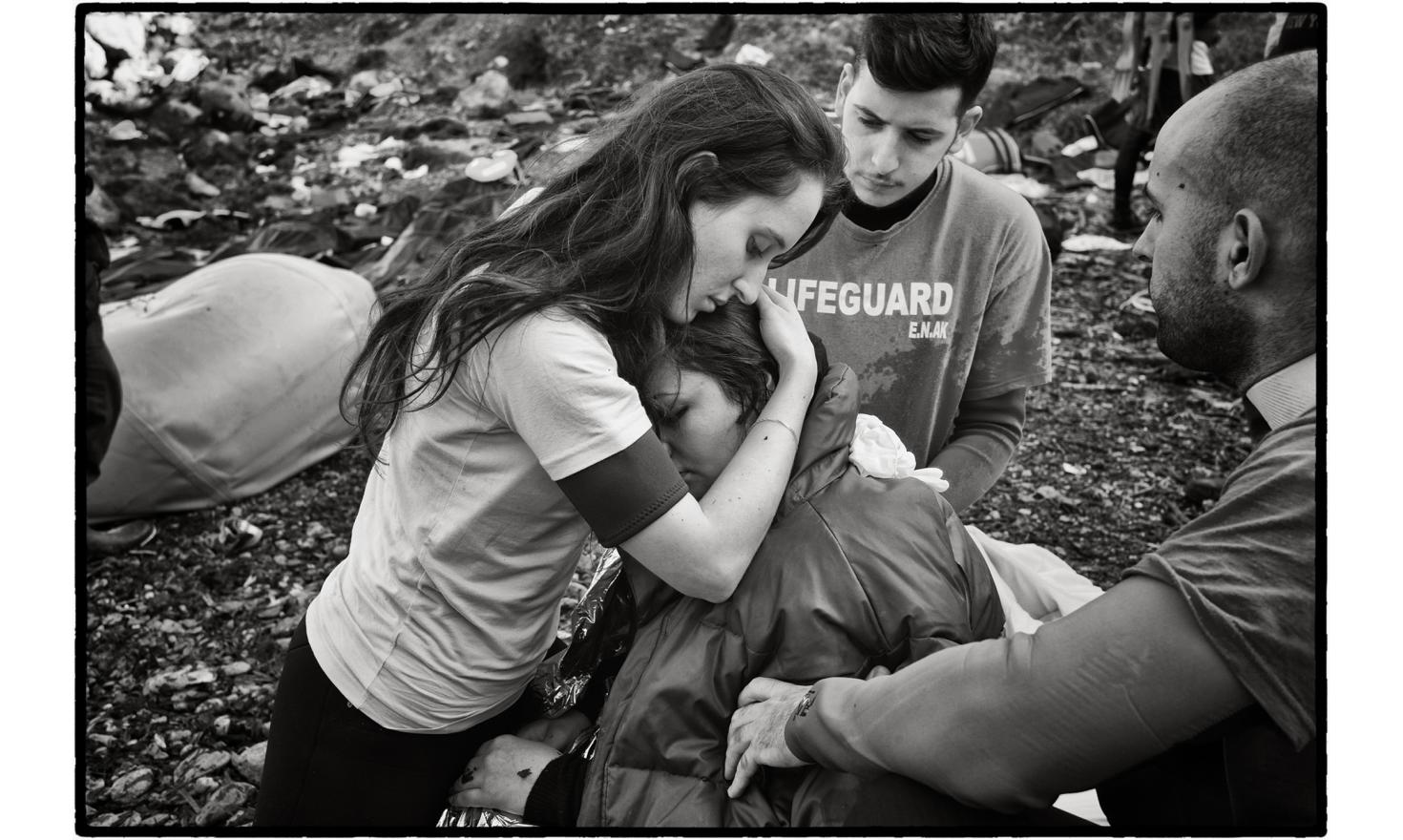 Lesbos, Greece. A young Greek volunteer from the sea rescue corps comforts an Iraqi refugee. Sunduz, 34 years old, a Kurd from Iraq, fled Mosul and Daesh three months ago with her husband and their two young children. Pregnant and in a state of shock afte