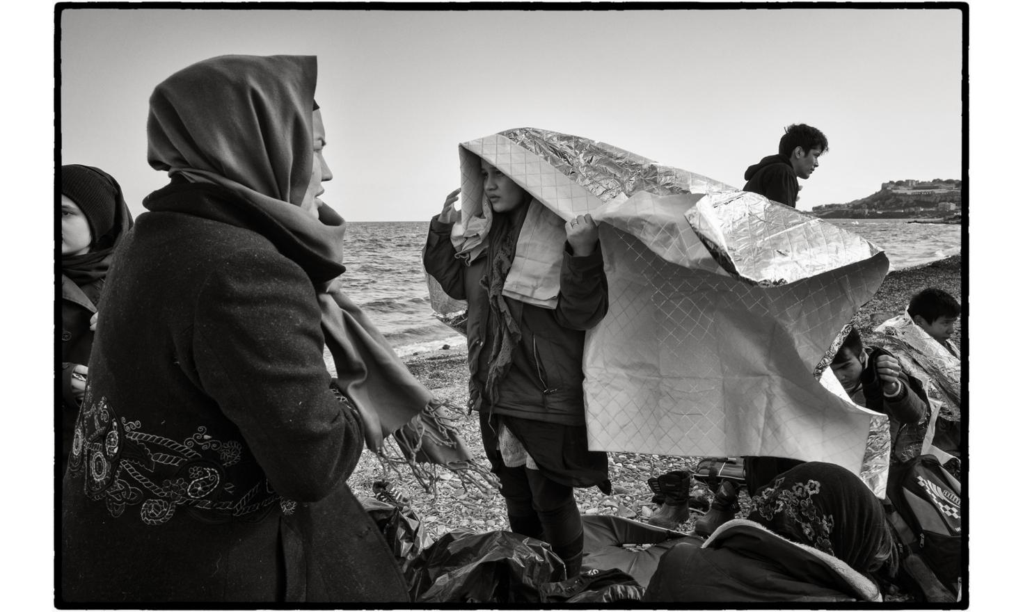Lesbos, Greece. On their arrival they are met by volunteers from all over Europe, who help them disembark from the boats and hand out survival blankets, hot drinks, fruit and sweets.